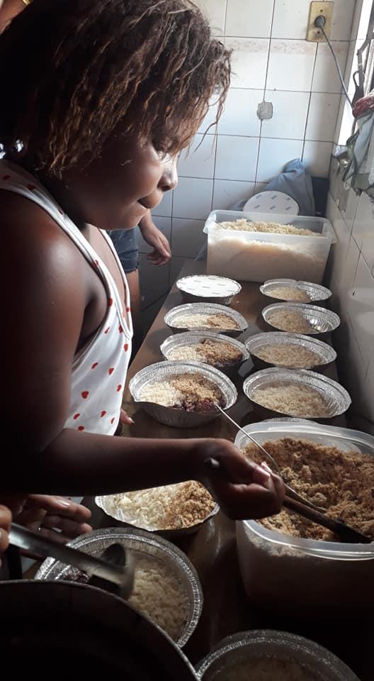 Menina distribui comida a sem-abrigo