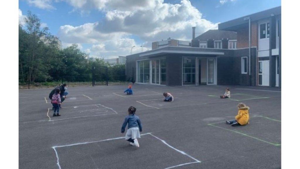 Crianças brincam na escola separadas por quadrados